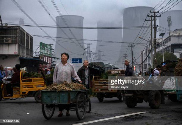 Chinese street vendors sell vegetables at a local market outside a state owned Coal fired power plant near the site of a large floating solar farm...