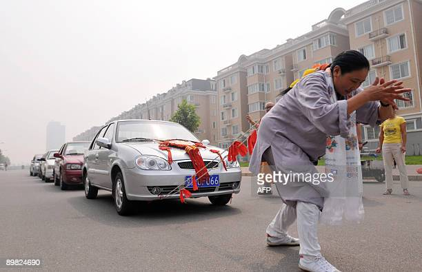 Chinese strongwoman Zhang Tingting pulls six cars with her hair over a distance of 50 metres in Beijing on August 15 2009 The feat has been performed...