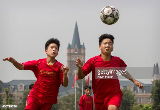 Chinese student heads the ball during training on the main pitch at the Evergrande International Football School on June 14 2014 near Qingyuan in...