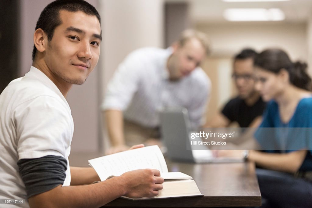 Chinese student reading book at desk : Stock Photo