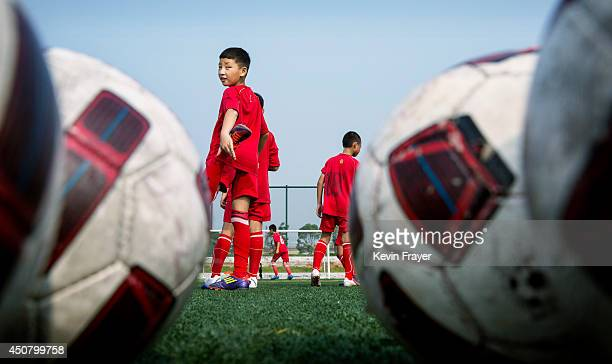 Chinese student waits his turn during training on the main pitch at the Evergrande International Football School on June 14 2014 near Qingyuan in...