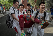 Chinese students joke with each other as they carry one student after completing the Gaokao at the Beijing Renmin University Affiliated High School...
