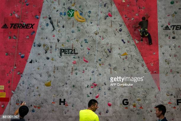 Chinese students practice on a climbing wall at the Shanghai Stadium in Shanghai on August 14 2017 / AFP PHOTO / CHANDAN KHANNA