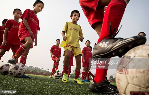 Chinese students with their turn as they practice before a training match at the Evergrande International Football School on June 14 2014 near...