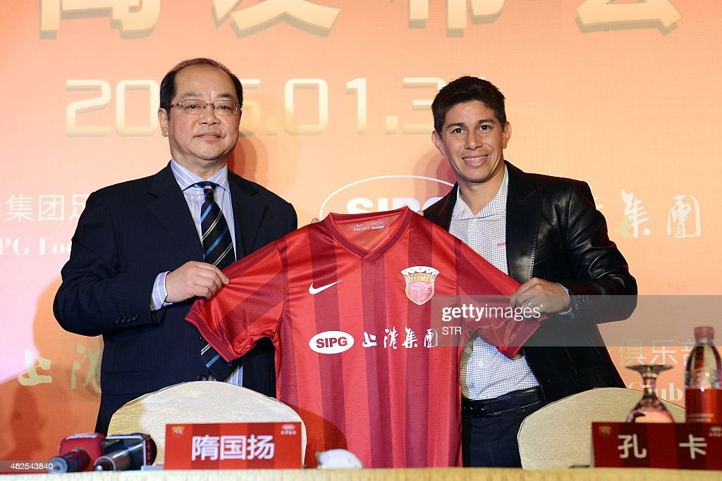 Chinese Super League football club Shanghai SIPG team manager Sui Guoyang poses with Argentine star Dario Conca after he signed to play for the club...