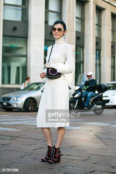 Chinese supermodel Ming Xi attends the Salvatore Ferragamo show at Piazza Affari in a Ferragamo white dress small purse and burgundy heels during...