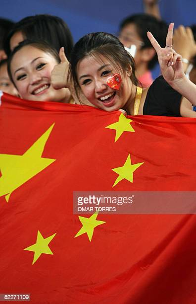 Chinese supporters hold they country flag as they celebrate China's Zhong Man's victory over France's Nicolas Lopez in the men's individual Sabre...