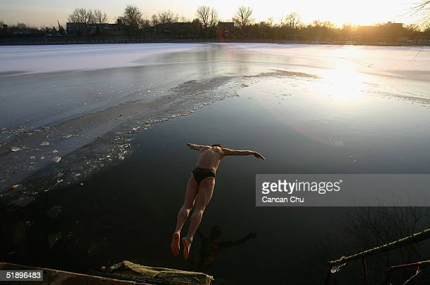 Chinese swimmer jumps into the frozen waters of Shishahai Lake December 27 2004 in Beijing China The lake is a popular spot for people who love...