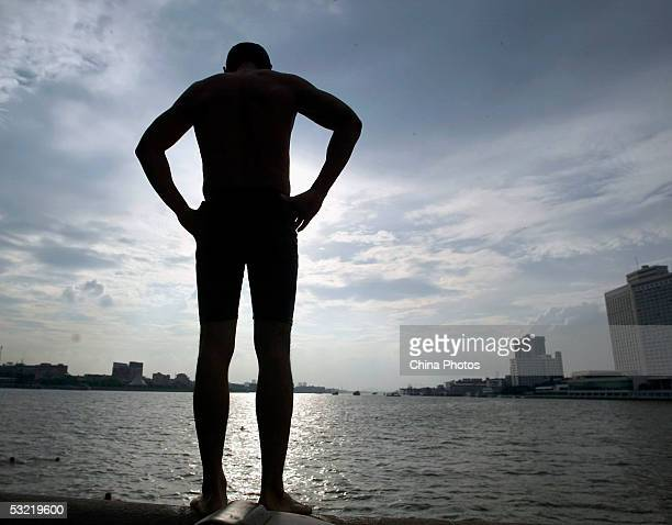 A Chinese swimmer prepares to dive into the Pearl River at the Zhoutouzui Dock on July 9 2005 in Guangzhou of Guangdong Province China Heatwaves have...