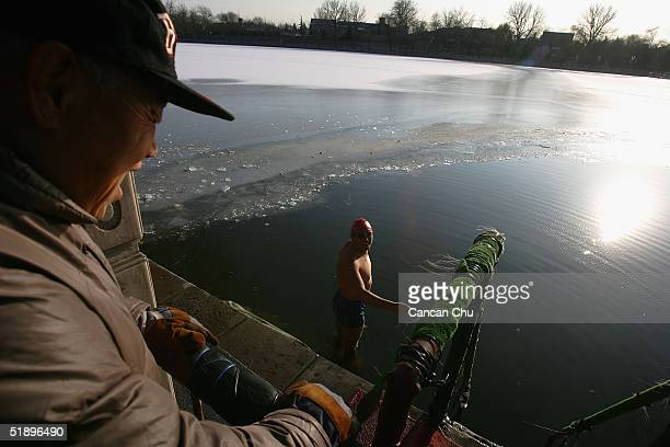 Chinese swimmer speaks with a friend before jumping into the frozen waters of Shishahai Lake December 27 2004 in Beijing China The lake is a popular...