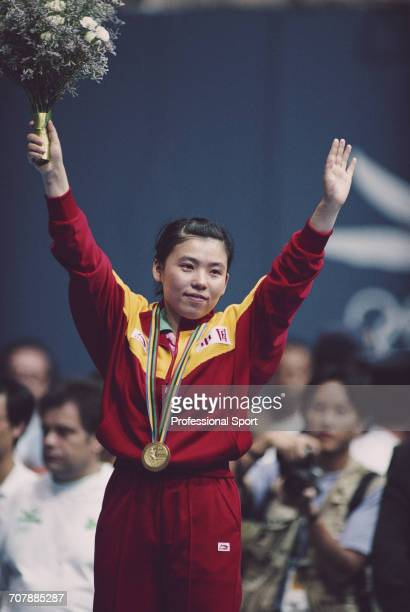 Chinese table tennis player Deng Yaping raises her arms in the air on the medal podium after competing for China to win the gold medal in the Women's...