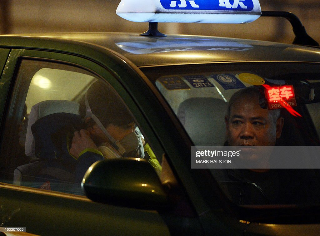 A Chinese taxi driver (R) watches as a man puts on a face mask before leaving the cab in the central business district during heavy air pollution in Beijing on January 30, 2013. Beijing urged residents to stay indoors as emergency measures were rolled out aimed at countering a heavy cloud of smog blanketing the Chinese capital and swathes of the country. The municipal government said children, the elderly and people sensitive to poor air quality should remain indoors, after authorities announced the closure of 103 factories and ordered 30 percent of official cars off the road. AFP PHOTO/Mark RALSTON