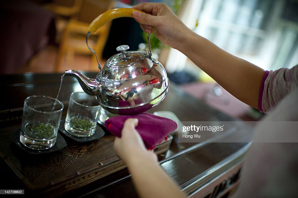 A Chinese tea ceremony master displays Longjing tea ceremony during a tea appreciation event at China National Tea Musem on March 30, 2012 in Hangzhou, China. Longjing is a green-tea, often called Dragon Well tea. The tea is typically picked by hand, and is of a high quality, earning the title of China Famous Tea. The Longjing tea begins to pluck before Chinese traditional Qingming Festival, the 15th day from the Spring Equinox or usually occurring around April 5. Many Chinese migrant workers from Jiangsu, Anhui, Jiangxi and other neighboring provices have been employed with 80 RMB yuan(US$12.68) to 120 RMB yuan(US$ 19.03) per day to pluck fresh Longjing tea leaves for villagers in many Longjing tea production villages in the outskirts of Hangzhou. The price of Longjing tea rose in recent years which aims to become to luxury goods. A high-end Longjing tea in Hangzhou sold for 50,000 RMB yuan(US$ 7930) half a kilo in 2012, the price rose 70 times in the last 12 years.