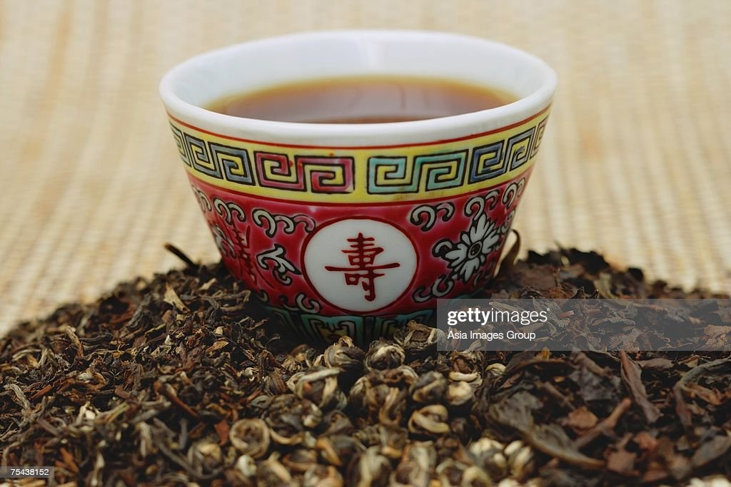 Chinese teacup and pile of loose tea leaves : Stock Photo