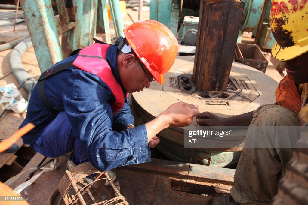 A Chinese technician with China Railway Major Bridge Engineering Company Limited (MBEC), Li Shaoxun, measures the depth of one of the piers on the construction site of a bridge at Kurasini area in Dar es Salaam on March 23, 2013. The bridge with a total length of 680m will have six dual-way motor lanes and double-sided pavements.
