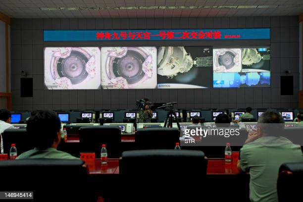 Chinese technicians at the Jiuquan Space Centre monitor the Shenzhou9 spacecraft as it prepares to link with the Tiangong1 module just over a week...