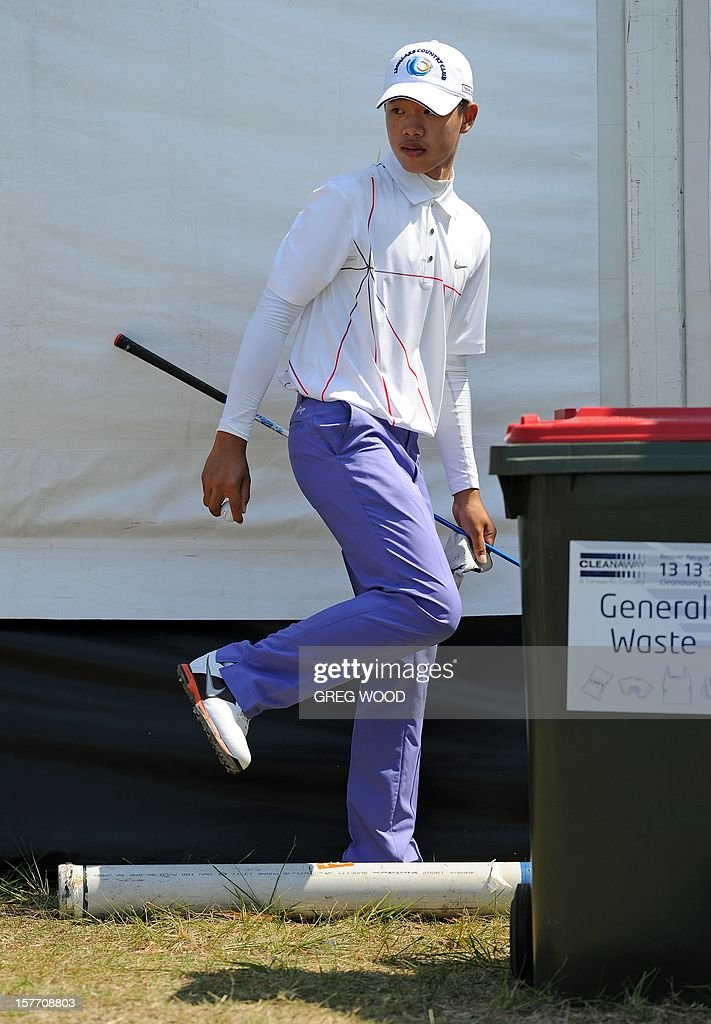 Chinese teen golfing sensation Guan Tianlang retrieves his ball which landed behind a bin during round one of the Australian Open golf at The Lakes course in Sydney on December 6, 2012. IMAGE STRICTLY RESTRICTED TO EDITORIAL USE - STRICTLY NO COMMERCIAL USE AFP PHOTO / Greg WOOD