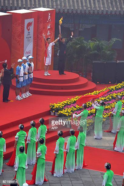 Chinese test pilot Li Zhonghua holds up the Olympic torch as the day's first torchbearer to take the flame along a section of the Great Wall in...