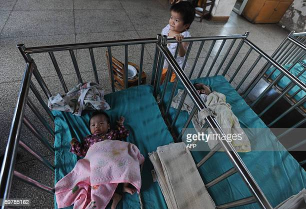 Chinese toddlers rest in their cribs at an orphanage in Wuhu eastern China's Anhui province on August 7 2009 China has for many years been an...