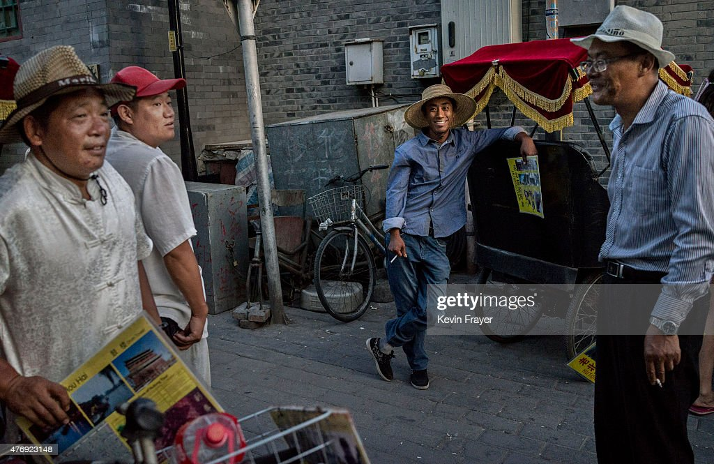 Chinese tour guides wait for customers in a gentrified hutong or tradtional neighbourhood on June 12 2015 in Beijing China Many of the traditonal...