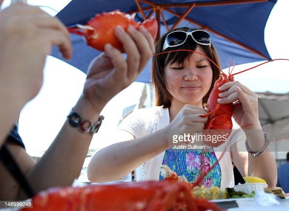 Chinese tourist Anna Ng enjoys freshly cooked Maine lobsters at the Portland Lobster Company on July 21 2012 in Portland Maine A mild winter and...