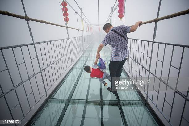 A Chinese tourist holds onto his son as they walk across a glassbottomed suspension bridge in the Shiniuzhai mountains in Pingjiang county Hunan...