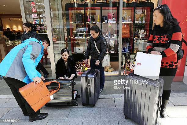 A Chinese tourist left prepares to pack a handbag into a suitcase outside a Laox Co store in the Ginza district of Tokyo Japan on Monday Feb 16 2015...