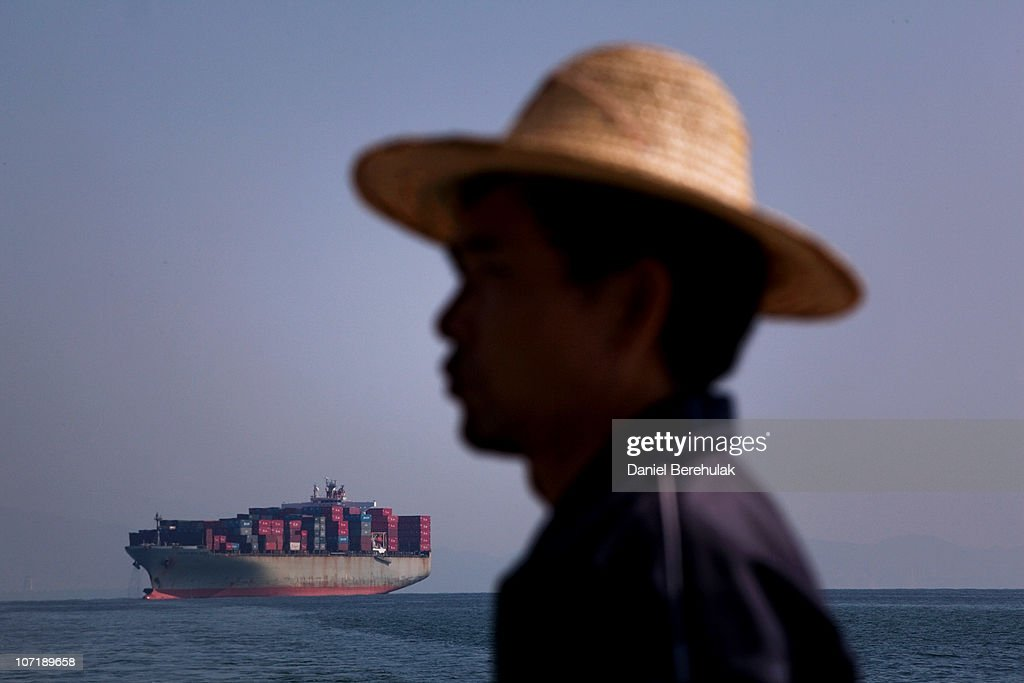 A Chinese tourist looks on as the Golden Gate Panama cargo ship navigates its way into Shenzhen Port on November 28, 2010 in Shenzhen, China. According to the US Commercial Service, Shenzhen is one of the fastest growing cities in the world. Home of the Shenzhen Stock Exchange and the headquarters of numerous technology companies, the now bustling former fishing village is considered southern China's major financial centre.