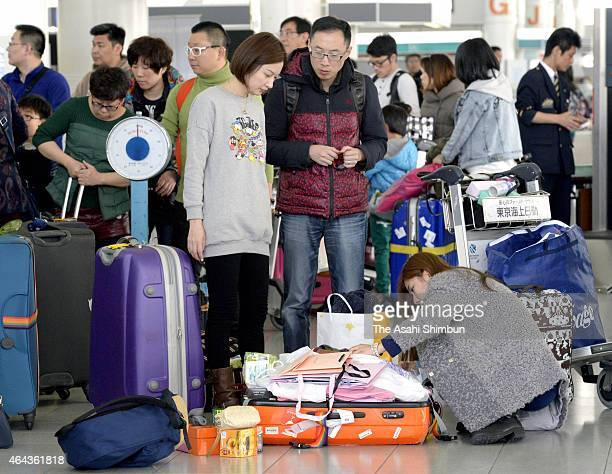 A Chinese tourist opens her suitcase at a departure lobby at Fukuoka Airport on February 24 2015 in Fukuoka Japan Driven by the weaker yen and eased...