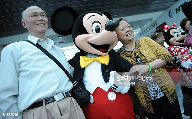 A Chinese tourist poses with Mickey Mouse during the National Tour Association and the Travel Industry Association cruise with the first Chinese...