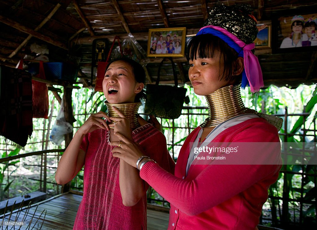 A Chinese Tourist reacts as she tries on a the heavy long neck gold band during a visit to the Baan Tong Luang Hiill tribe village on September 4, 2012 in Maerim, Thailand. Baan Tong Luang is a fabricated village containing 6 separate Thai Hill Tribes where visitors are expected to pay $16 or 500 Thai bhat for the entrance fee. Some of the ethnic tribes include the Lahu, Hmong, White Karen, Long necked Karen, Yao, and Akha. The village opened in 2005 attempting to preserve the old traditions of the ethnic Hill Tribe, while providing an income for them. Visitors must pay an entry fee of 500 Thai that or $16. Life for many of Thailand's Hill Tribe population can be difficult since it can be hard for them to make a living. Their language, costume and culture are different along with the frequent legal problems over Thai citizenship. Hill tribe is a term used in Thailand for all of the various tribal peoples who migrated from Tibet, or elsewhere in China over the past few centuries.