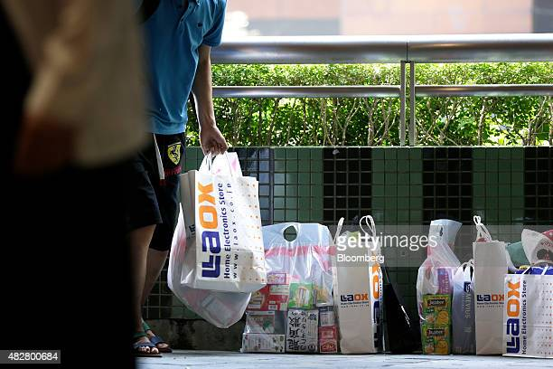 A Chinese tourist stands next to shopping bags at the Canal City Hakata commercial complex in Fukuoka Japan on Friday July 24 2015 Four million...