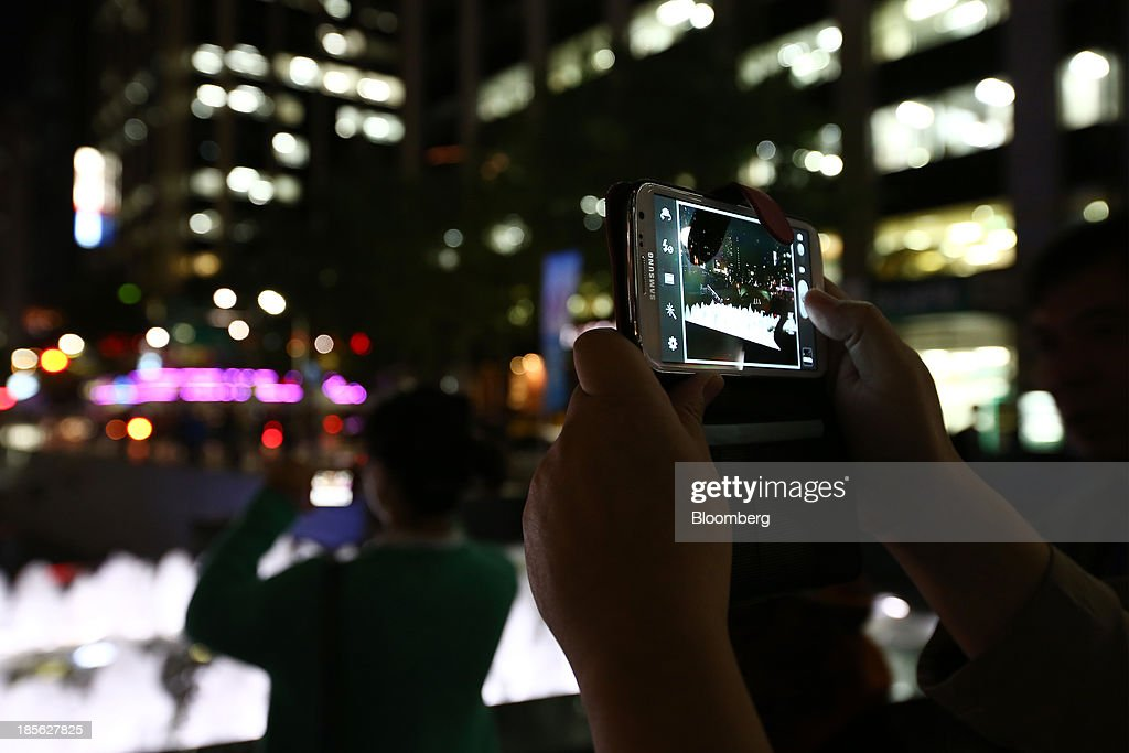 A Chinese tourist takes a photograph of Cheonggye Stream using his Samsung Electronics Co. Galaxy Note 2 smartphone at night in Seoul, South Korea, on Tuesday, Oct. 22, 2013. Samsung Electronics is scheduled to release third-quarter earnings on Oct. 25. Photographer: SeongJoon Cho/Bloomberg via Getty Images