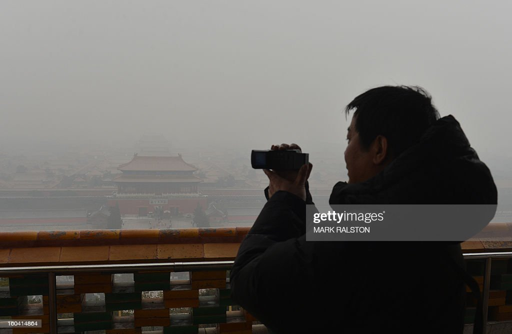 A Chinese tourist takes photos of the Forbidden City from the historic Jingshan Park as smog continues to shroud Beijing on January 31, 2013. Doctors in Beijing said on January 31 that hospital admissions for respiratory complaints rose in recent days during the latest bout of air pollution to cover northern China. AFP PHOTO/Mark RALSTON