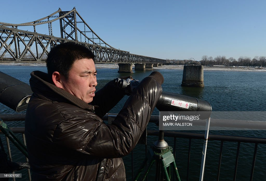 A Chinese tourist views North Korea from the old the Sino-Korean Friendship bridge that was destroyed by the US Air Force in 1950 and used to link the North Korean town of Sinuiju with the Chinese town of Dandong on February 10, 2013. US Secretary of State John Kerry warned that North Korea's expected nuclear tests only increase the risk of conflict and would do nothing to help the country's stricken people. The country has vowed to carry out a third nuclear test soon, and concerns have been raised over the type of fissile material used in the device. AFP PHOTO/Mark RALSTON