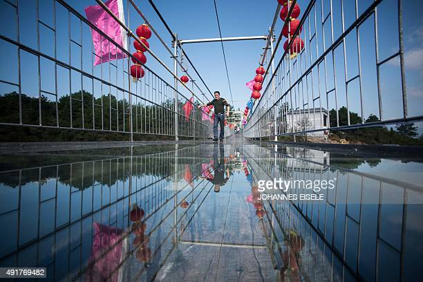 A Chinese tourist walks across a glassbottomed suspension bridge in the Shiniuzhai mountains in Pingjiang county Hunan province some 150 kilometers...