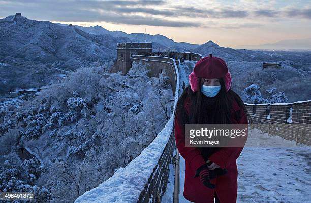 Chinese tourist walks on a slippery section of ice as snow is seen on the Great Wall after a snowfall on November 23 2015 near Beijing China China's...