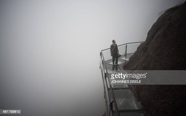 A Chinese tourist walks over a glass bottomed skywalk in the Shiniuzhai mountains in Pingjiang county Hunan province some 150 kilometers from...