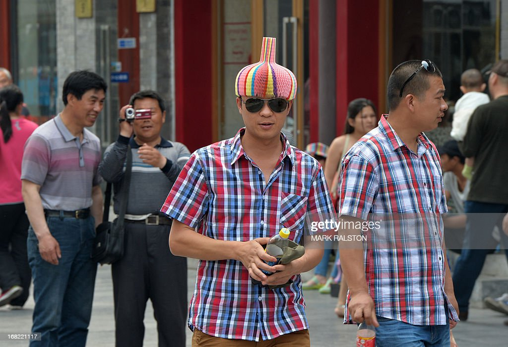 A Chinese tourist wearing a colourful hat visits the historic Qianmen district of Beijing on May 7, 2013. China is now the third most visited country in the world with the number of overseas tourists visiting totaling nearly 60 million annually and the number of domestic tourist visits at 1.61 billion according to the World Trade Organization (WTO). AFP PHOTO/Mark RALSTON