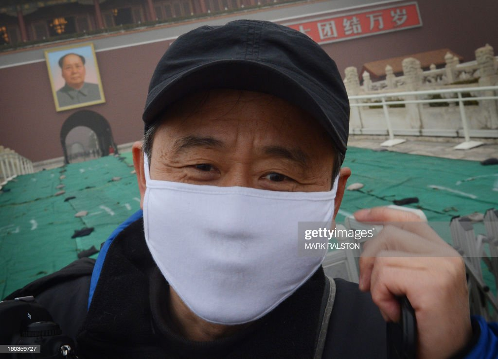 A Chinese tourist wears a face mask as he visits Tiananmen Gate and the portrait of Mao Zedong during heavy air pollution in Beijing on January 30, 2013. Beijing urged residents to stay indoors on January 30 as emergency measures were rolled out aimed at countering a heavy cloud of smog blanketing the Chinese capital and swathes of the country. AFP PHOTO/Mark RALSTON