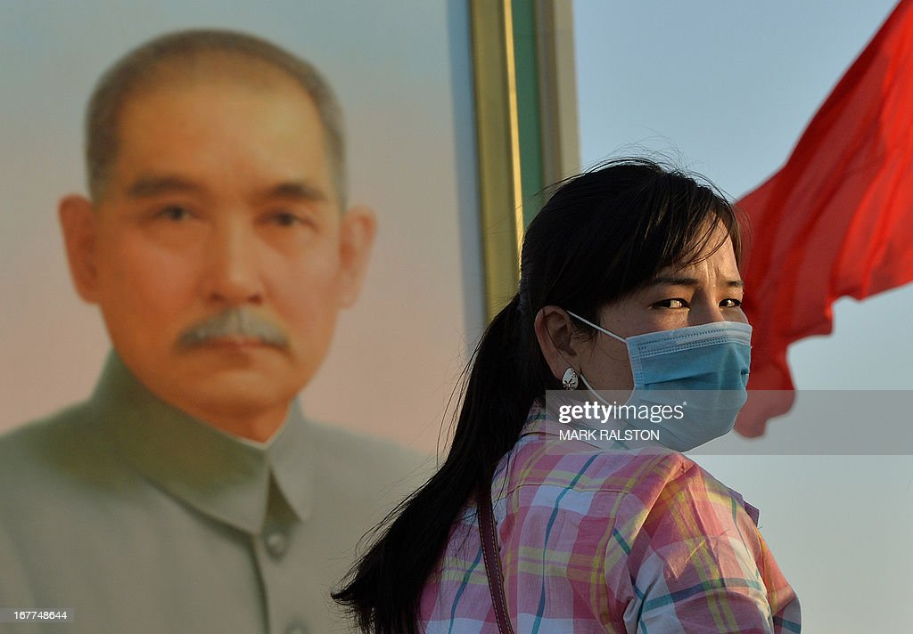 A Chinese tourist wears a face mask in front of a portrait of revolutionary leader Sun Yat-sen at Tiananmen Square in Beijing on April 29, 2013. There is no evidence that the deadly H7N9 bird flu has yet spread between humans in China but health authorities must be ready for the virus to mutate at any time, top US virologist Anthony Fauci has warned. AFP PHOTO/Mark RALSTON