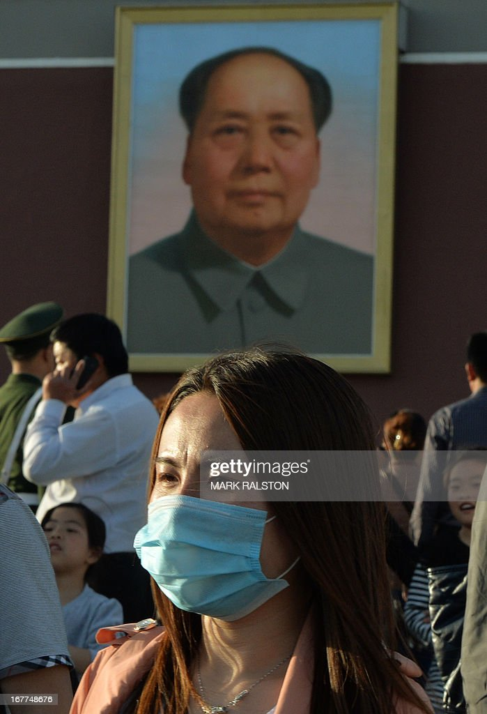 A Chinese tourist wears a face mask in front of a portrait of revolutionary leader Mao Zedong at Tiananmen Square in Beijing on April 29, 2013. There is no evidence that the deadly H7N9 bird flu has yet spread between humans in China but health authorities must be ready for the virus to mutate at any time, top US virologist Anthony Fauci has warned. AFP PHOTO/Mark RALSTON
