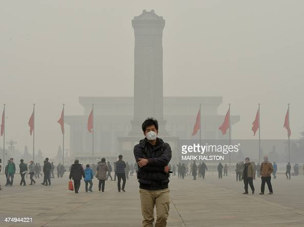 A Chinese tourist wears a face mask in Tiananmen Square as heavy air pollution continues to shroud Beijing on February 26 2014 Beijing's official...