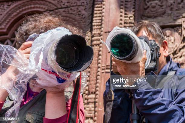 Chinese tourists are taking photographs of thousands of young people smeared and playing with color celebrating the Holi Festival