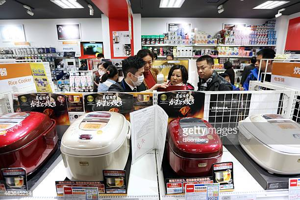 Chinese tourists browse rice cookers on display at a Laox Co store in the Ginza district of Tokyo Japan on Monday Feb 16 2015 Foreign visitors to...