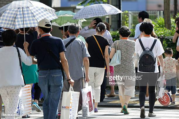 Chinese tourists carrying shopping bags cross a road as they leave the Canal City Hakata commercial complex in Fukuoka Japan on Friday July 24 2015...