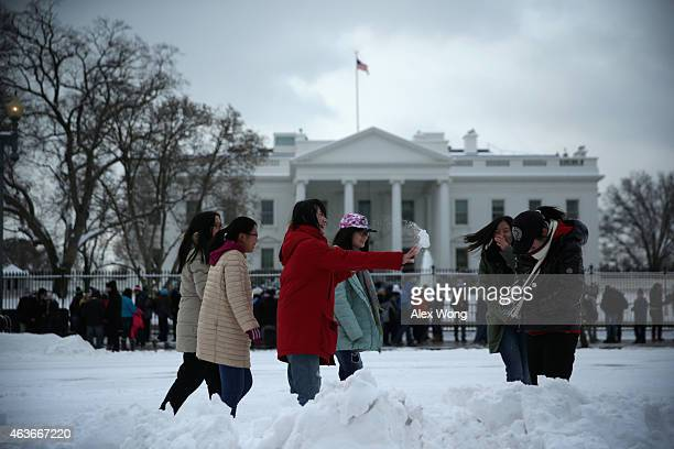 Chinese tourists from Beijing participate in a snowball fight in front of the White House February 17 2015 in Washington DC The first major snow...