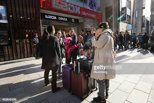 Chinese tourists gathered around luggage stand waiting for a tour bus outside a Laox Co store in the Ginza district of Tokyo Japan on Monday Feb 16...