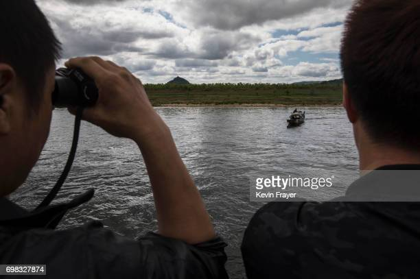Chinese tourists look at a North Korean fisherman as they ride in a boat on the Yalu river with North Korean territory on both sides north of the...