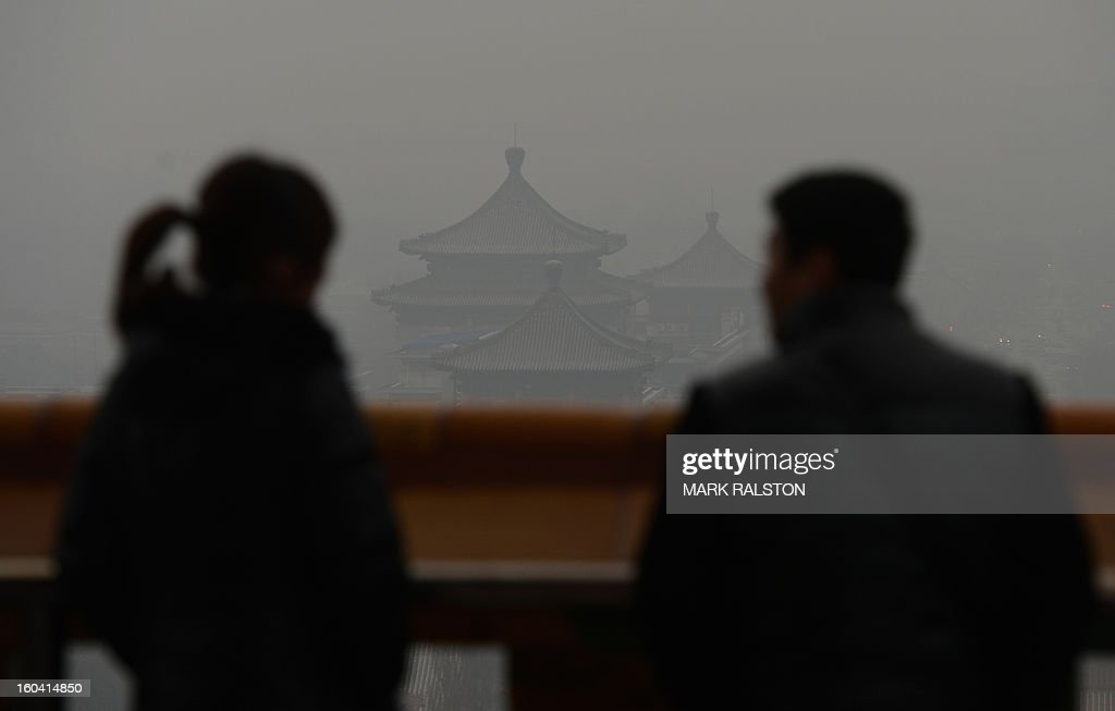 Chinese tourists look at the view from the historic Jingshan Park as smog continues to shroud Beijing on January 31, 2013. Doctors in Beijing said on January 31 that hospital admissions for respiratory complaints rose in recent days during the latest bout of air pollution to cover northern China. AFP PHOTO/Mark RALSTON